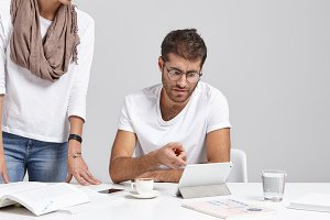 Young Caucasian bearded boss in glasses and t-shirt sitting at white office with diagram and tablet on desk, pointing at mistake in calculations of report made by his unrecognizable woman employee