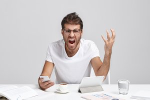 Picture of annoyed bearded male wearing glasses and casual white t-shirt sitting at his workplace holding mobile phone, screaming loudly, feeling fed up and irritated, having stressful working day