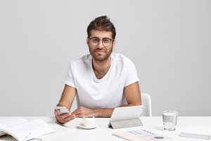 Handsome hipster guy freelancer working at home office, sitting in modern interior and using electronic gadgets, looking and smiling at camera. Happy male student chatting online using cell phone
