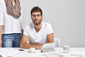 Confident young bsinessman with earring and stubble studying documents at office with mug of coffee, electronic gadgets and papers on desk, his unrecognizable female assistant standing behind him