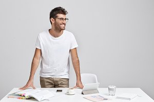 Unshaven positive young male teacher in glasses and casual clothes standing at desk in classroom and looking sideways with cheerful smile after lesson with his student&#x3B; gadgets and textbooks on table