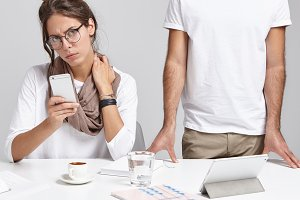 Business, job, occupation, teamwork and cooperation concept. Stylish young woman in glasses having concentrated look using cell phone while working on start up project with unrecognizable man