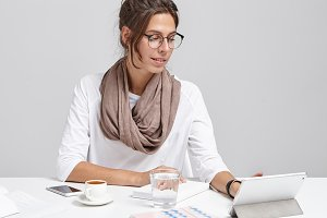 Stylish business lady wears glasses, sits at work place, uses modern digital tablet for preparing business report, drinks coffee during break, makes arrangment with business partners and companions