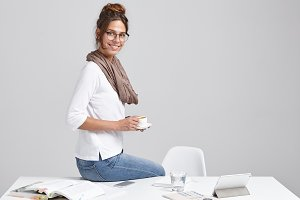 Portrait of beautiful young female creative worker wearing jeans sitting on her desk and enjoying morning coffee feeling excited about new day, plans, goals and achievements. Time for coffee break
