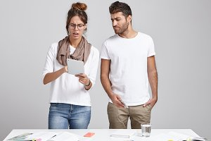 Candid shot of two coworkers man and woman discussing project on digital device, standing side by side at light office. Concentrated female in glasses showing something on touchpad to male colleague