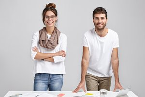 Cooperating and working in team. Two successful enthusiastic creative startuppers male and female standing at white desk in modern office interior, having happy looks, renjoying good results