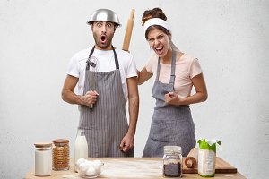 Family couple have quarrel at kitchen: irritated female shouting at lazy husband, threaten with rolling pin. Scared man recieving punishment from wife after coming home late. Cooking concept