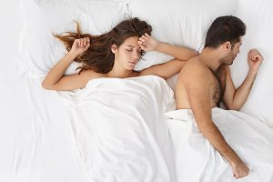 Exhausted family couple have sweet dream, being tired after hard working day, enjoy good rest in bed. Attractive young woman and handsome bearded man sleep together after unforgettable night