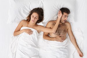 Attractive tired male and female having sweet dreams, lying in bed side by side on white bedclothes. High angle view of peaceful European couple sleeping comfortably in bed at home or hotel room