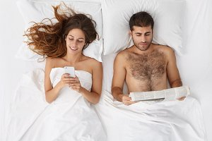People, relationships, leisure and vacation concept. Happy newly married couple relaxing in hotel room on honeymoon: husband reading newspaper and wife messaging online using smart phone in bed