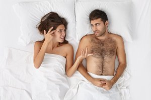 Top view of irritated woman complaining while lying in bed with her bearded husband. Frustrated European married couple quarreling in bedrroom having irritated annoyed expressions on their faces