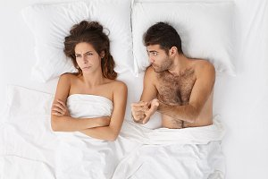 Top view of family couple has argue and misunderstanding in bed. Annoyed female doesn`t want to hear her husband who proves guiltlessness. Irritated woman and man have relationships difficulties