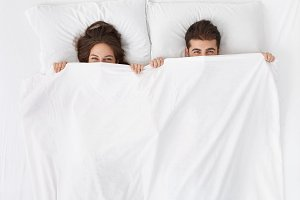 Funny married couple lying in bed and hiding under white blanket, looking at camera with eyes full of joy. Attractive Caucasian man and woman having fun in bedroom. Love and happiness concept