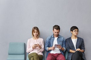 People, employment, recruitment, technology concept. Three unemployed people sit in queue, wait for job interview, use modern gadgets, prepare answers on tricky questions from boss or employer