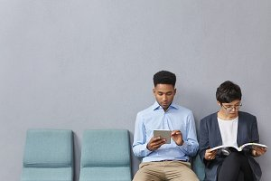 Afro American guy with tablet and brunette female read magazine sit together as wait for job interview. Two young applicants getting prepared for communication with director of business company