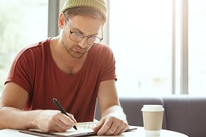 Young talented copywriter puts down ideas in notebook, sits at coffee shop, looks seriously at notes. Attractive hipster in stylish clothing being busy with writing, arranges meetings with people