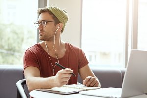 Portrait of fashionable male worker uses laptop to listen to his favorite music online in earphones writes notes in notebook, looks aside as notices someone outdoors. Stylish student prepares for exam