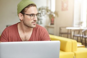 Portrait of talented male journalist works on article, types information at laptop computer, wears spectacles, looks pensively aside as tries to gather thoughts, sits at work place. People and work