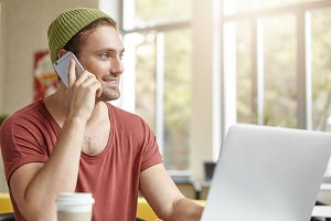 Indoor shot of stylish hipster guy with beard, wears hat and t-shirt, calls his friend over smart phone, sits in restaurant, works on laptop computer and drinks coffee. Technology and communication