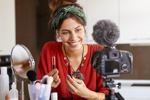 Attractive cheerful popular young woman video blogger advertising beauty products via her blog on social media, holding two lip gloss, comparing their quality, looking at camera fixed on tripod