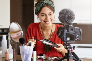 Indoor shot of glad woman sits at home, uses cosmetic products for making video diary, looks at camera with appealing smile. Elegant female applies eyeshadow, shows for women its great effect