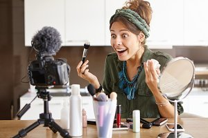 Excited young Caucasian fashion blogger looking at camera fixed on tripod having amazed expression while applying powder presenting daily make up, sitting at dressing table with cosmetic products