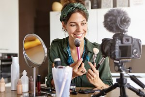 Candid shot of beautiful young female cosmetologist tests new kind of powder brushes, films process on video camera, smiles broadly. Delightful blogger advertises cosmetic products for viewers