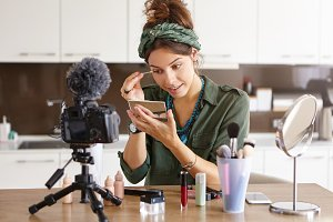 Attractive talented female blogger does make up, reviews beauty product for video blog, gives advice to girls and women, films process on camera. Fashionable woman has online translation at home