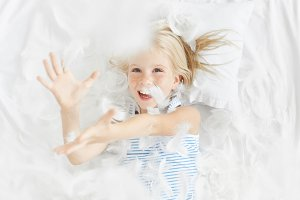 Indoor shot of carefree little blonde girl with blue eyes plays in bedroom, catches feather in air, being amused by father and mother. Naughty child tears pillow into pieces. Children`s behaviour