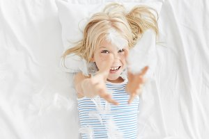 Lovely charming 5-year old Caucasian girl with blonde hair and freckled face lying on white bedclothes in her bedroom and playing with feathers, throwing or catching them, having playful happy look
