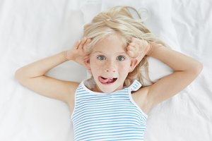 High angle view of funny adorable blonde freckled blue eyed European little girl dressed in striped pajamas having fun in hre bedroom, making faces, looking at camera and sticking out tongue