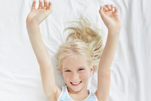 Happy cute little girl with fair hair and freckles stretching arms after sleep, lying on white bedclothes in her room. Blonde freckled child waking up in the morning, smiling cheerfully at camera
