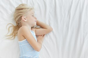 Profile portrait of cute 7-year old baby girl with light hair sleeping comfortably in her bed, having sweet dreams and smiling, lying on cotton bedcloth with copy space for your text or content