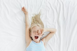 Top view of cute blonde little girl stretching in white bed, yawning and rubbing her eyes, awaking early in the morning before going to kindergarten. Bedtime, awakening and relaxation concept
