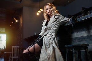 Beautiful blond woman in gray coat sitting near bar counter