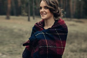 Girl walking in the park. Girl wearing plaid. Pretty woman in the forest.