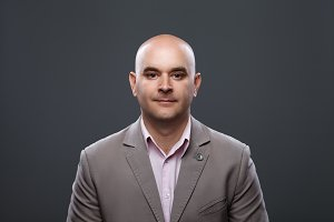 Portrait of a bald affable man in a suit against a dark background