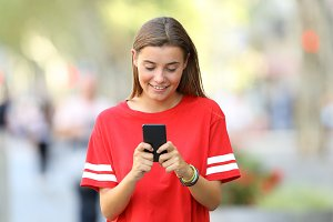 Front view of a happy teen texting