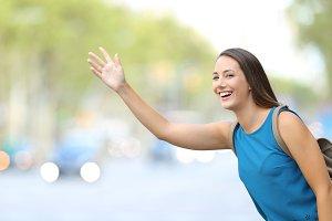 Single happy woman hailing taxi