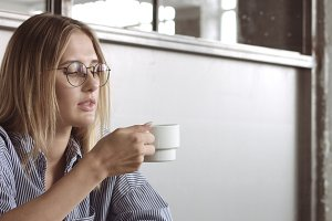 A blond pretty model drinks some coffee