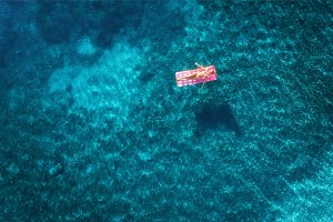 Aerial view of young woman swimming on the pink inflatable mattr
