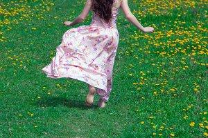 the barefoot girl runs on a grass