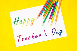 Concept of Teachers Day. Caption: A happy teacher's day surrounded by colors, pencils, pens, school objects.