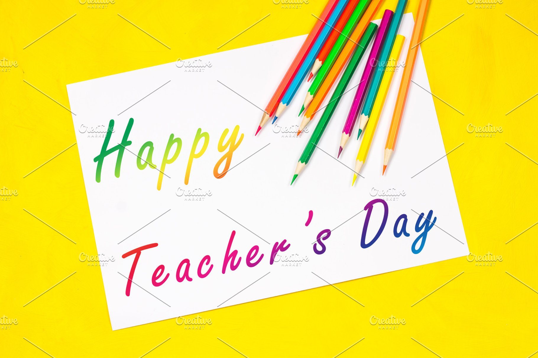 Concept of Teachers Day  Caption: A happy teacher's day surrounded by  colors, pencils, pens, school objects