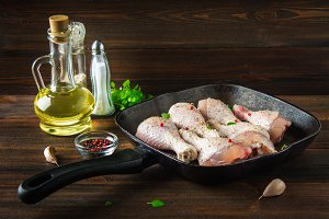 Raw chicken legs in a frying pan on a wooden table. Meat ingredients for cooking.