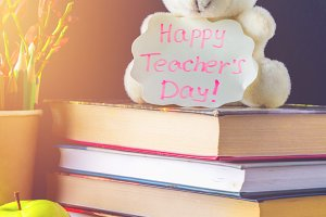 Concept of Teacher's Day. Objects on a chalkboard background. Books, green apple, bear with a sign: Happy Teacher's Day, pencils and pens in a glass, twig with autumn leaves.