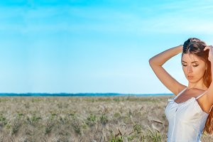 Beautiful summer girl wheat field, white dress, tanned skin, happy on vacation fresh air. A sunny day. The concept of harmony.