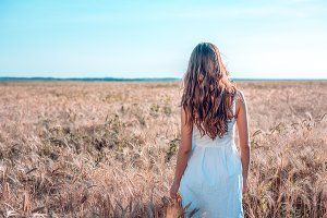 The girl in summer wheat field, white dress, tanned skin, goes to field, happy on vacation in fresh air. A sunny day. The concept of harmony. It is back.