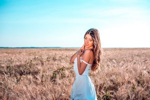 Happiness nature summer vacation - young woman in a white dress field sunny day in nature, concept of tenderness. Feminine silhouette of tanned skin.