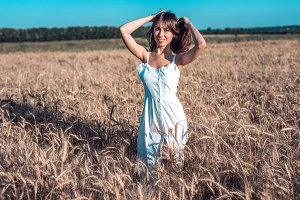 Beautiful happy woman in a field, sunny afternoon, white dress. Beautiful hair, tanned skin, concept of enjoying nature. Rest on the air. Harmony with wheat.